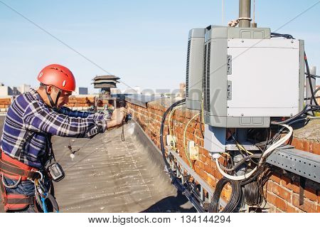 worker finished work and takes photos for the report. quality control. tower technician installed telecommunication equipment on the roof of the building. a good worker photographed the completed part of the work to check