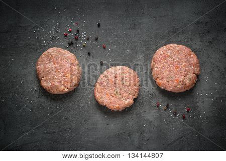Cutlet. Raw beef and pork burgers and ingredients for cooking at slate background.