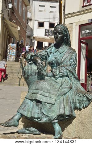 COIMBRA, PORTUGAL - AUGUST 3, 2016: Bronze statue of Portuguese woman in the historical center of Coimbra Portugal.