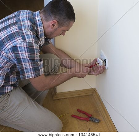 Electrician installing new current socket with screwdriver. Installing electrical outlet or socket - closeup on electrician hands