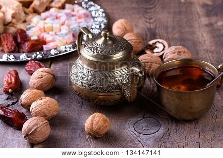 Traditional arabic tea set walnut and dried dates. Oriental sweet on silver plate. Turkish delight halva dates and others on old wooden background