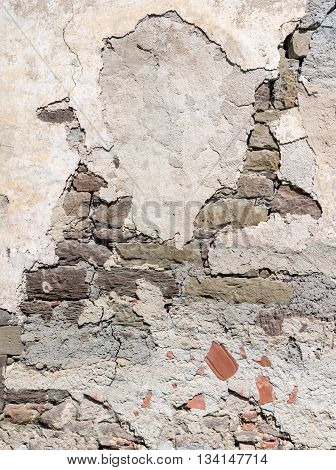 Detail of an old gray wall with partially crumbling plaster