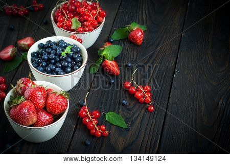 Three little bowls with different berries - strawberry blueberry and red currants.