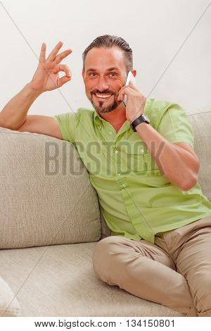 Portrait of handsome man happy smiling and showing okay sign while sitting on sofa or couch and speaking over mobile or smart phone at home.