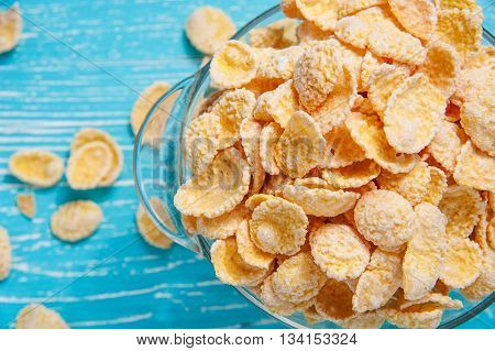 cornflakes on blue wooden table at morning top view closeup