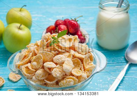 Bowl of cornflakes cereal on a blue wooden table and fresh strawberry apple milk behind.