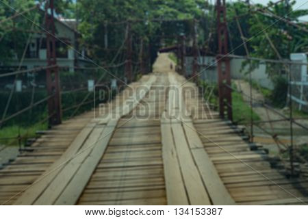 blurred image of cable sling wood bridge it main transportation between city to natural wild in Vang ViengLaos