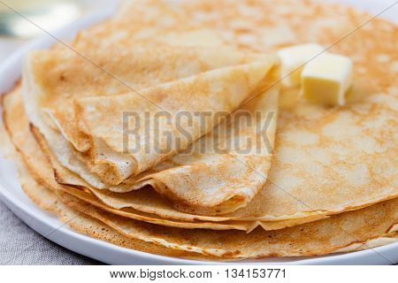 Thin crepes or pancakes with butter, honey and sour cream on a rustic textile background.