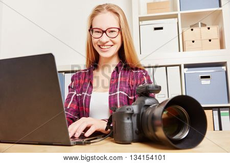 Women as a photographer doing data backup with a Laptop