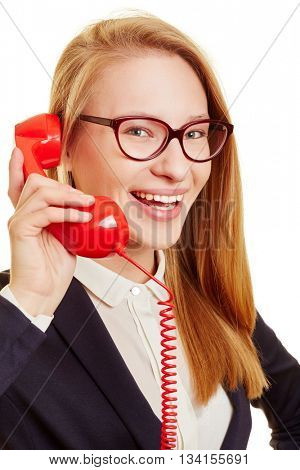 Happy businesswoman holding red telephone receiver and calling