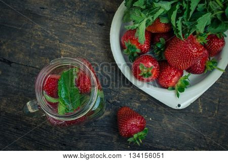 Refreshing summer drink with strawberry in mason jar on the vintage wooden table. Fresh strawberry drink on rustic background. Homemade drink with strawberry and mint in a mason jar. Top view.