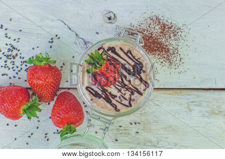 Homemade yogurt in a jar with strawberry, seeds and cacao. Dessert with strawberries on a white wooden background. Fresh juicy strawberry with yogurt. Top view. Copy space. Horizontal.