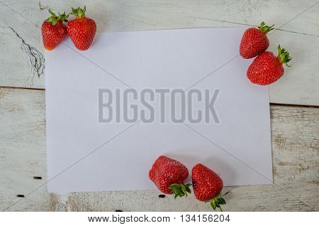 Red berry strawberry on white wooden background with sheet of paper. Background from freshly harvested strawberries with space for text. Strawberry background. Directly above. Top view. Copy space.