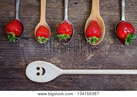 Strawberries on vintage spoons and wooden spoon with smiley face over old rustic wooden table top. Summer shades with hello summer happy colorful concept for summer season. Top view.
