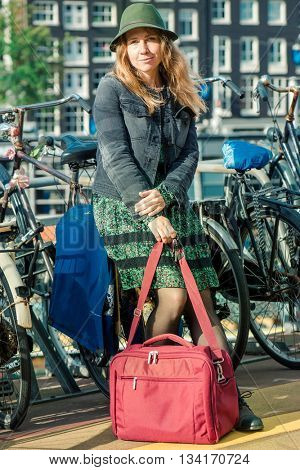 Tourist with a travel bag at a bicycle parking in Amsterdam, capital of the Netherlands