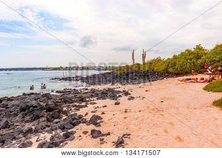 Puerto Ayora Santa Cruz Ecuador - April 11 2016: People at the beach called Playa de la Estacion. This is a nice little beach not far from the entrance to the Charles Darwin research center in Santa Cruz island in Galapagos