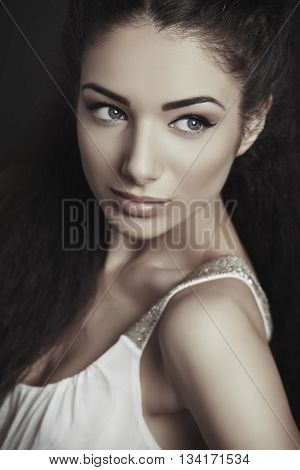 Portrait of attractive brunette young woman with blue eyes healthy skin looking sideways. Toned color.