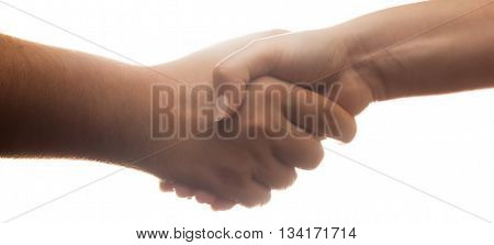 Candid handshake on white background. Strong backlight. Banner proportion.