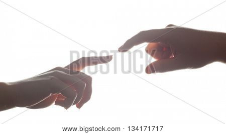 Man's and woman's hands, fingers reaching each other. Soft, gentle gesture in strong backlight. Love, connect, help concepts.