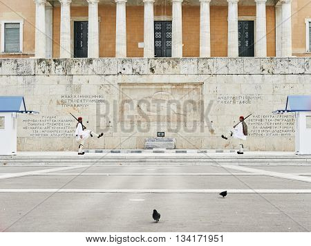 Athens Greece - March 27 2016: Perfect the coordination of movements during the changing of the honor Evzones guards ceremony in front of the Tomb of the Unknown Soldier at the Parliament Building in Syntagma Square Athens Greece.