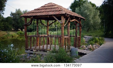 Wooden gazebo in the park by the lake summer afternoon