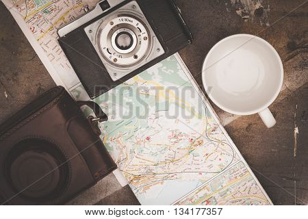 Vintage camera and map on wooden boards abstract background. Copy space for text. Top view. TONED Image.