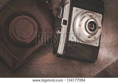 Vintage camera on wooden boards abstract background. Copy space for text. Top view. TONED Image.