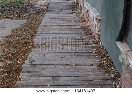 Wooden walkway lined with fallen brown leaves next to an abandoned building with bricks at the base
