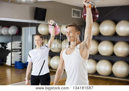 Man With Female Friend Lifting Kettlebell In Gymnasium