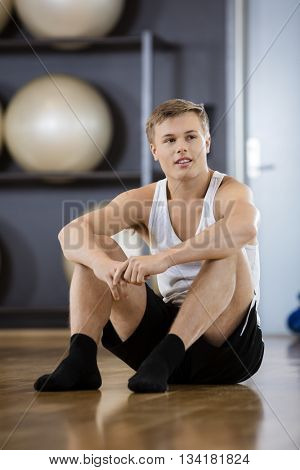 Thoughtful Tired Man Sitting On Floor In Gym