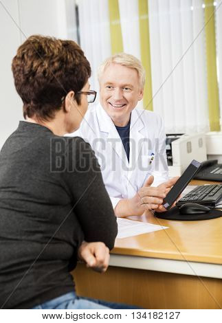 Doctor Showing Digital Tablet To Female Patient