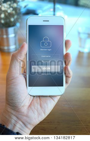 Hand holding smartphone with mebber loging screen on coffee shop background