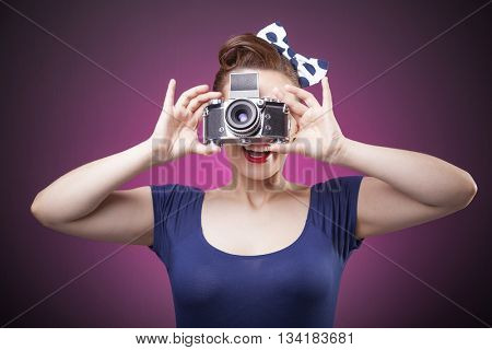 Pin Up girl taking photos with a vintage camera on pink background