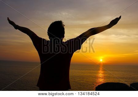 Silhouette Image of Man Raising His Hands, sunset background.