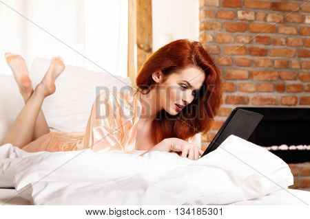 Beautiful Red-haired Woman Using Tablet Computer In The Bed