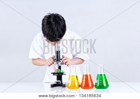 Asian boy conduct an experiment microscope and learning science experiment education