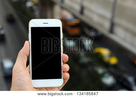 Hand holding smartphone with traffic jam background
