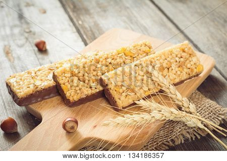 Chocolate granola bars with puffed cereals, cornflakes and rolled oats on wooden cutting board and golden wheat ears. Healthy food concept