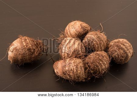 Heap of fresh taro roots (colocasia) on black background