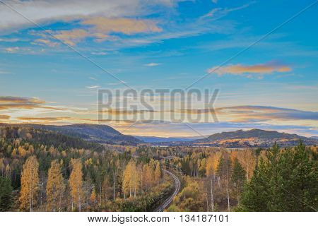 landscape with railbridge trees and mountains during sundown