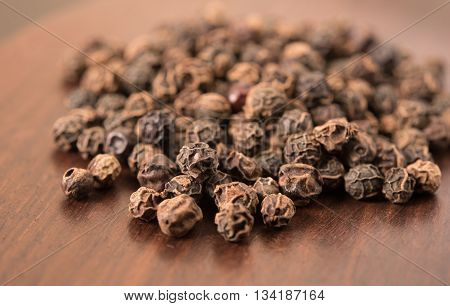 Dried Black pepper peppercorns on wooden background