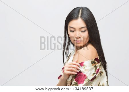 Portrit of fashion asian lady in dress demonstrating her shoulder and looking down in studio. Beautiful woman posing for photographer.