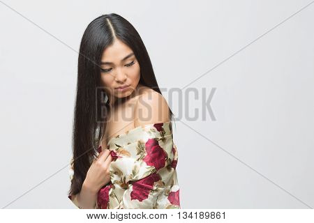 Beautiful and pretty asian lady posing in spring or summer dress in studio. Brunette lady looking down and posing for photographer.