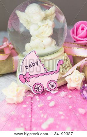 Pink wooden carriage figure with wrapped presents. Girl birth concept