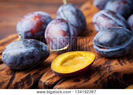 Fresh organic plums on rustic wooden cutting board.
