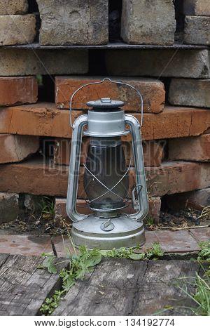 kerosene oil lamp near brick wall close up