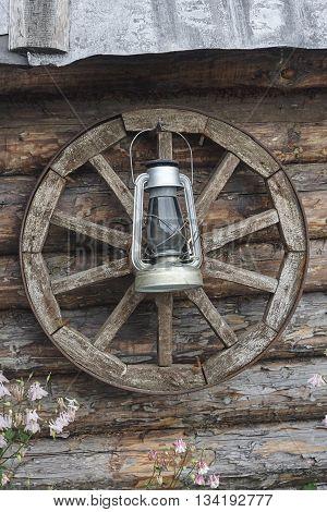 kerosene oil lamp and old wheel near wood wall close up