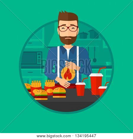 A hipster man suffering from heartburn. Man standing in the kitchen in front of table with junk food and suffering from heartburn. Vector flat design illustration in the circle isolated on background.