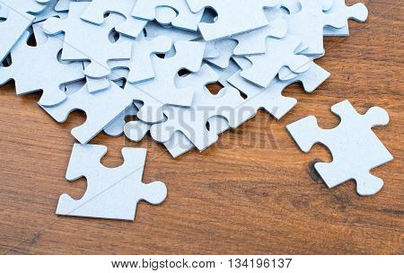 Pile of puzzle pieces on table, top view. Close-up