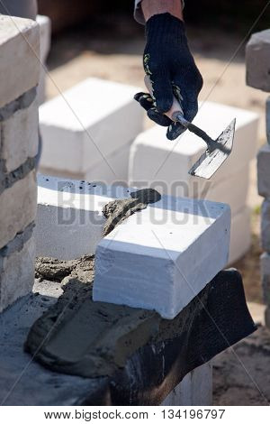 Builder lays Bricks in cement mortar